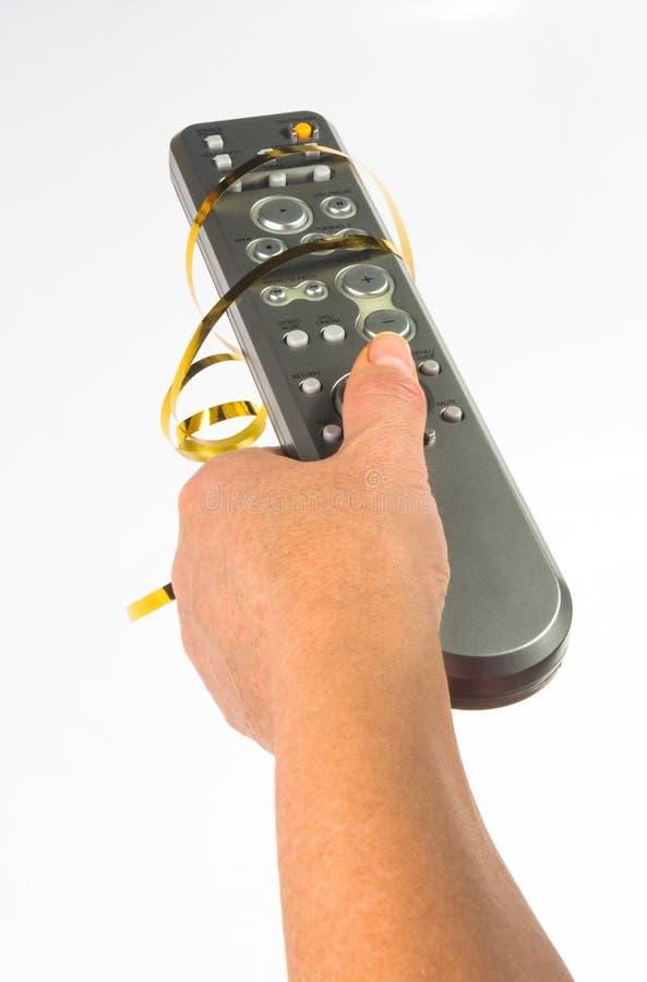 main tenant un à télécommande sur le fond blanc, en gros plan photos stock