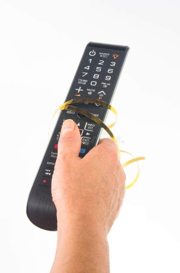 main tenant un à télécommande sur le fond blanc, en gros plan photos libres de droits