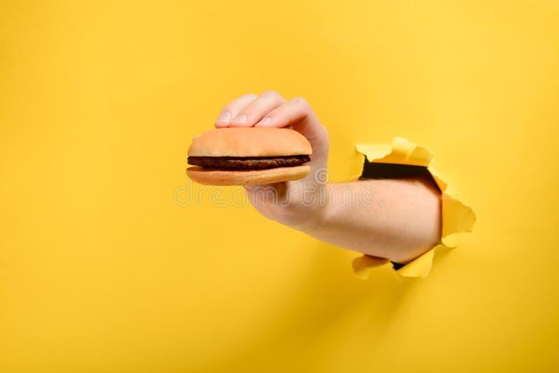 Main tenant un hamburger image stock