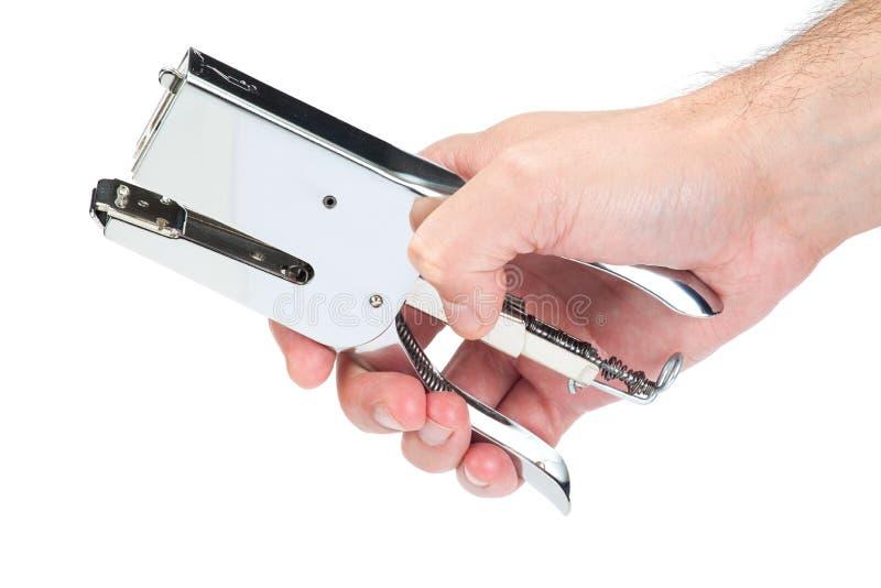 Main tenant une agrafeuse en métal photographie stock