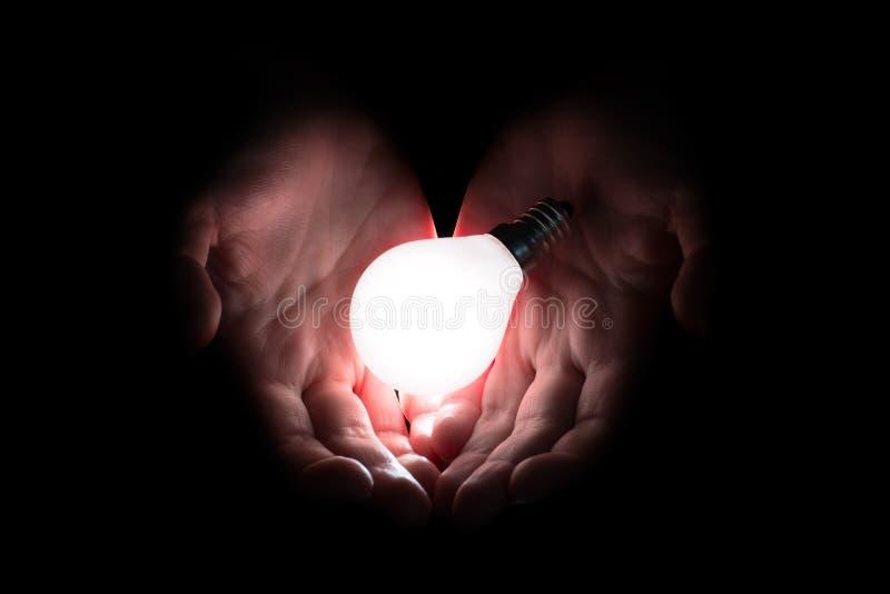 Main tenant une ampoule rougeoyante photographie stock libre de droits