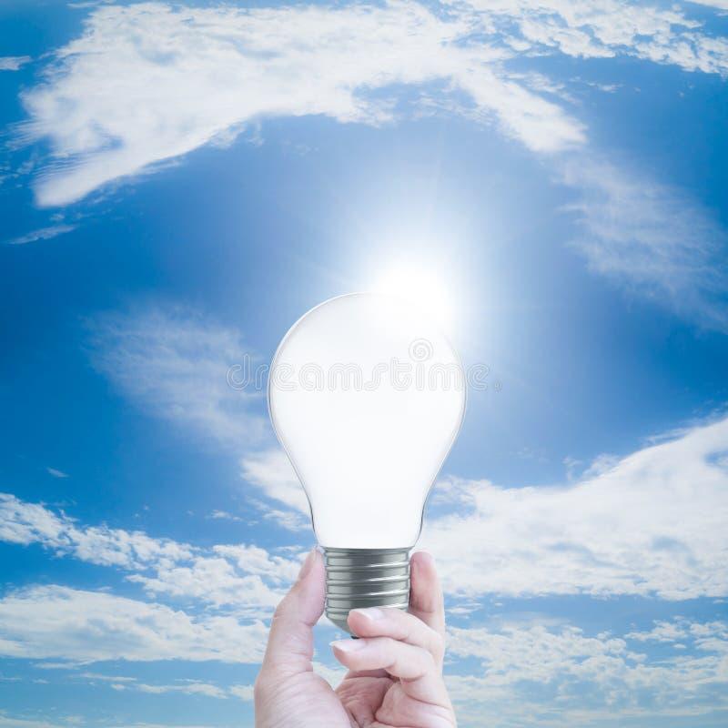 Main tenant une ampoule sur le fond de ciel bleu illustration de vecteur