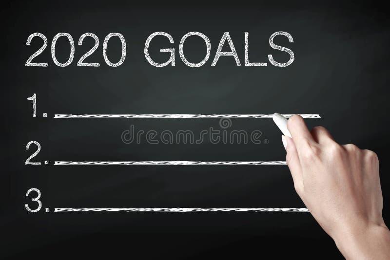 Main tenant une craie et écrivant 2020 buts photo stock