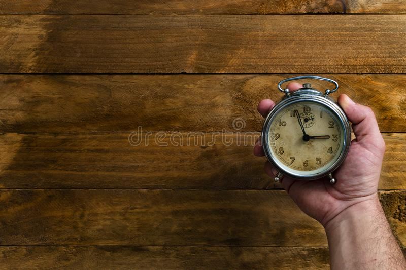 Main tenant une horloge antique image stock