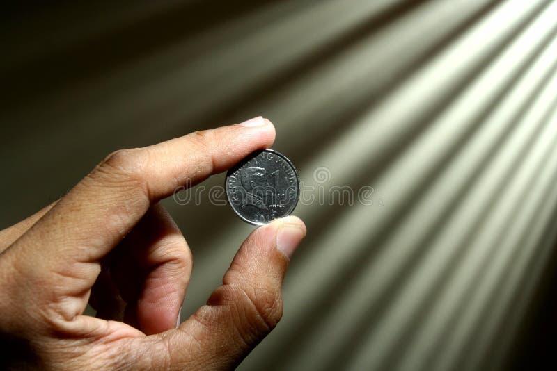 Main tenant une pièce de monnaie images stock