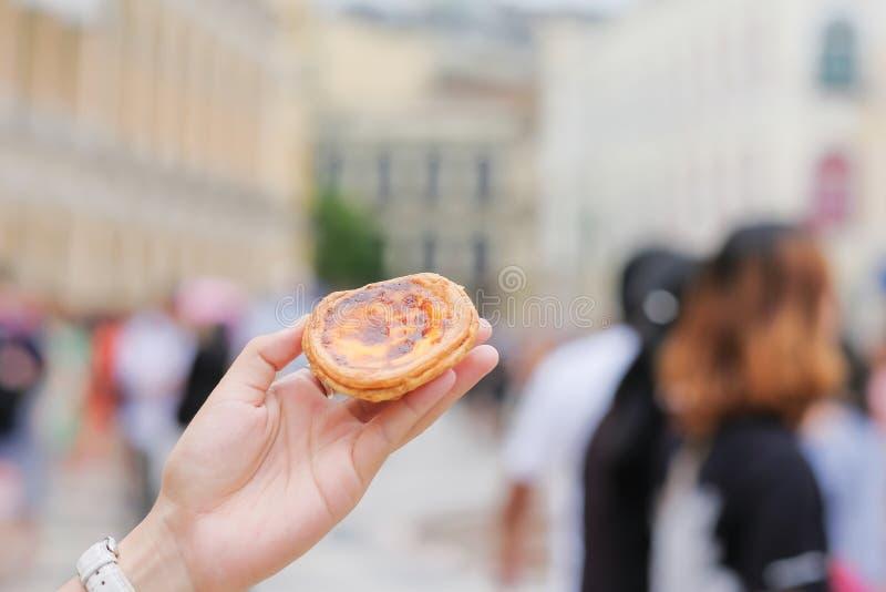 Main tenant une tarte d'oeufs, desserts portugais traditionnels célèbres à la place de senado dans Macao Point de repère et popul images stock