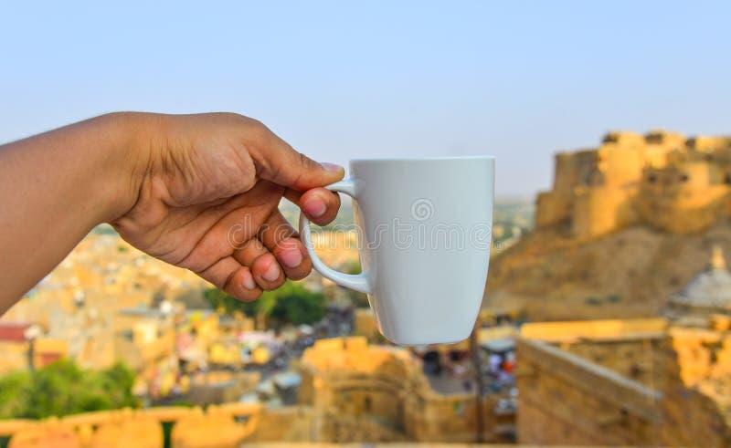 Main tenant une tasse blanche image libre de droits