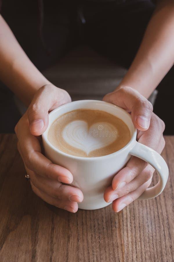 Main tenant une tasse de café avec du lait de mousse de coeur photos libres de droits