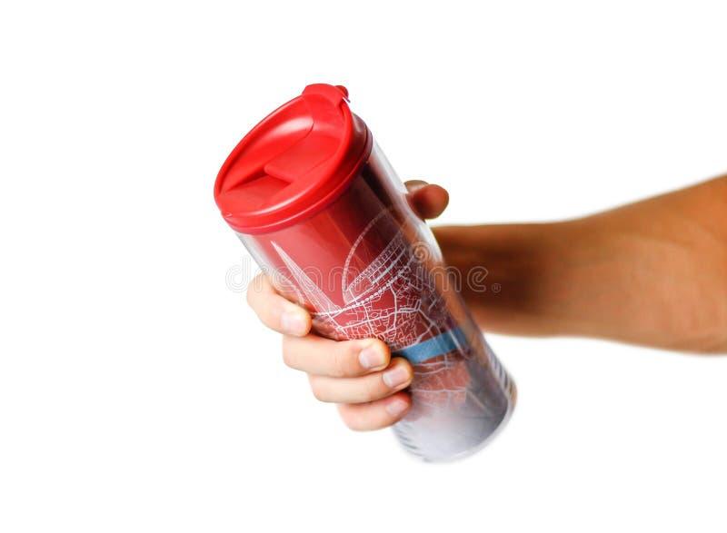 Main tenant une tasse thermo rouge Fin vers le haut D'isolement sur le fond blanc image stock