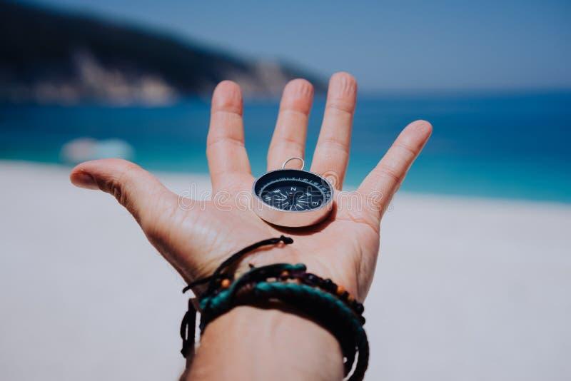 Main tendue tenant la boussole noire en métal contre la plage sablonneuse blanche et la mer bleue Trouvez votre concept de manièr photo stock