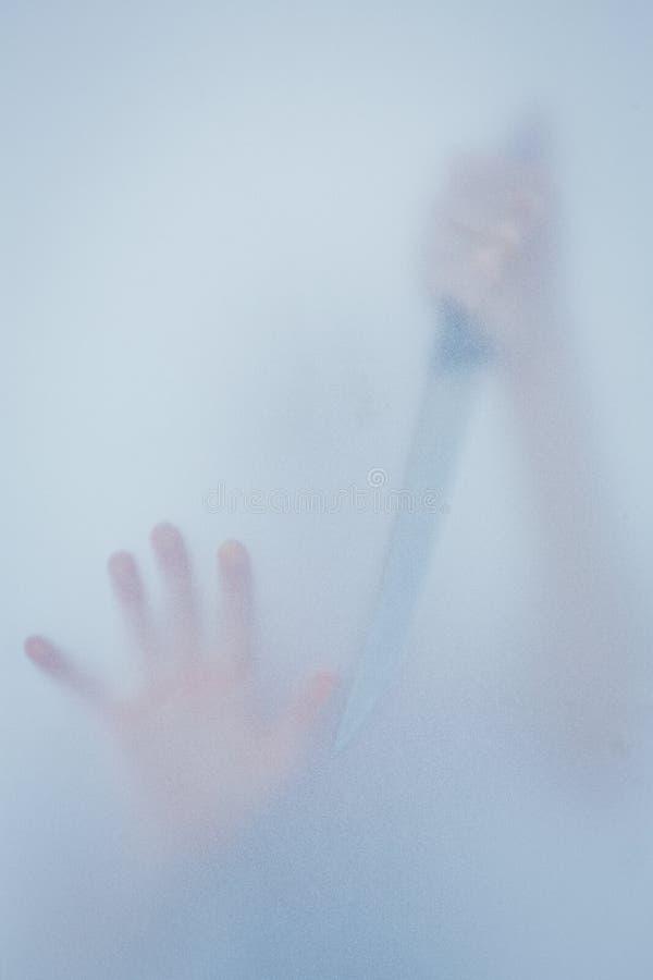 Main touchant le verre givré et tenant le couteau photographie stock