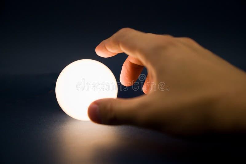 Main touchant une bille lumineuse photographie stock