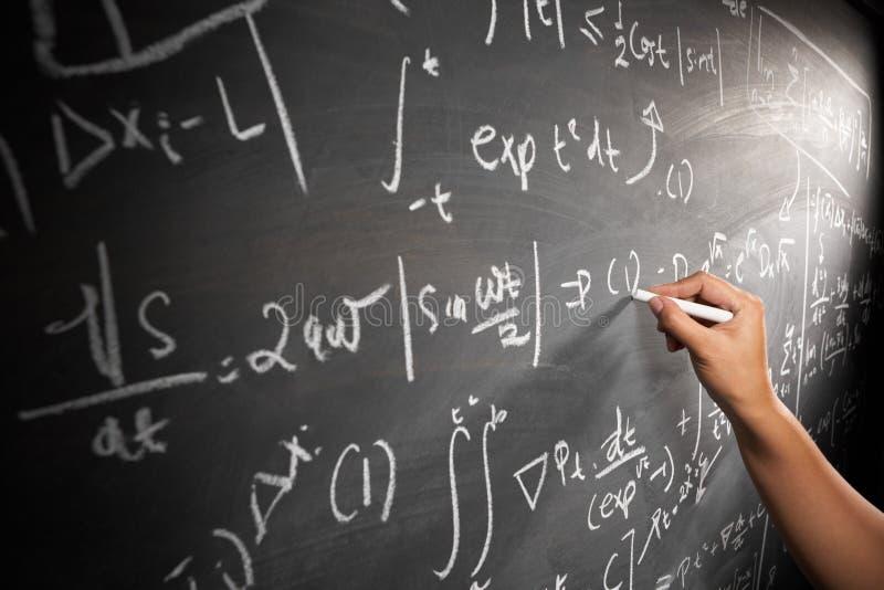 Main travaillant sur l'équation image stock
