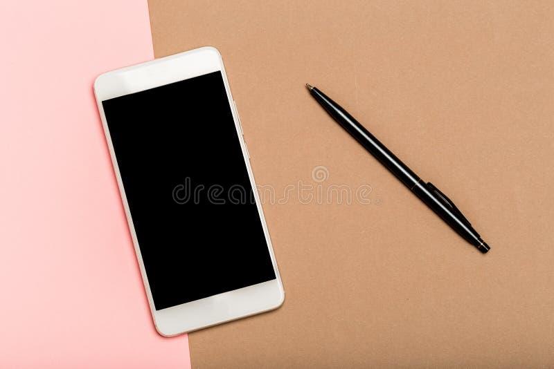 Main utilisant l'écran blanc de téléphone sur la vue supérieure, fond dans des couleurs en pastel, stylo photo stock