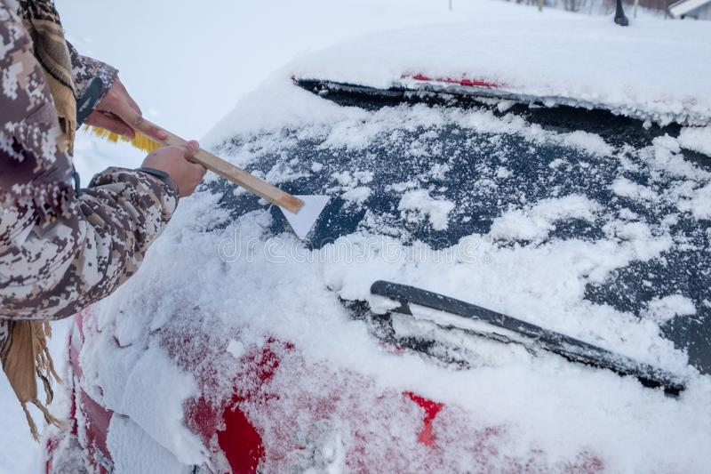 Main utilisant la neige de éraflure de Web sur le pare-brise arrière de voiture photo libre de droits