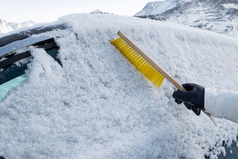 Main utilisant la neige rapide de brosse sur le pare-brise de voiture photographie stock libre de droits