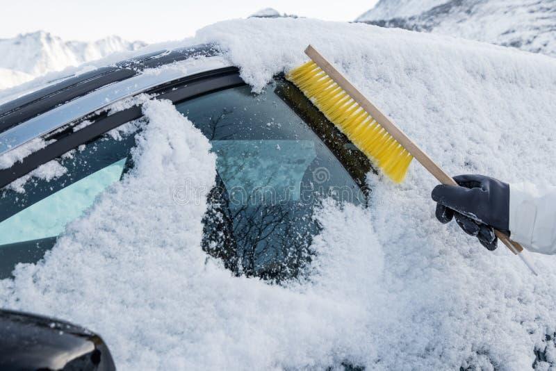 Main utilisant la neige rapide de brosse sur le pare-brise de voiture photo stock