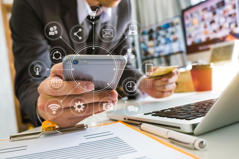 Main utilisant le comprimé, l'ordinateur portable, et tenir le smartphone avec le réseau de transmission de paiement d'opérations photo libre de droits