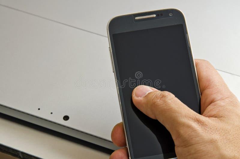 Main utilisant le smartphone avec l'ordinateur portable photographie stock libre de droits