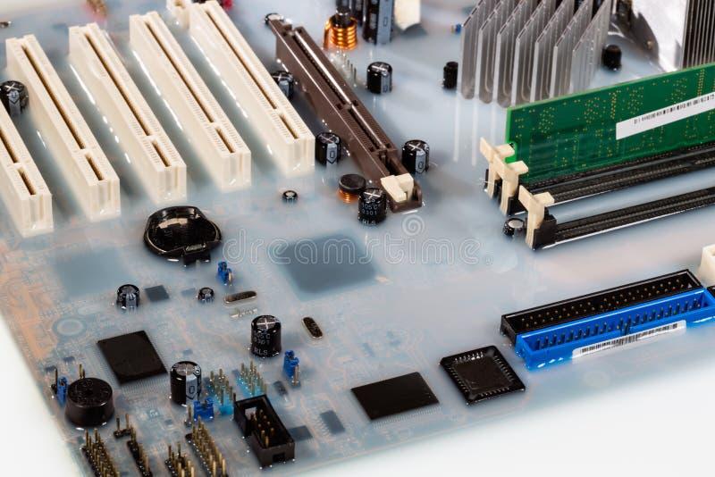 Mainboard card dator översvämmad av vitt färgat vatten arkivfoto