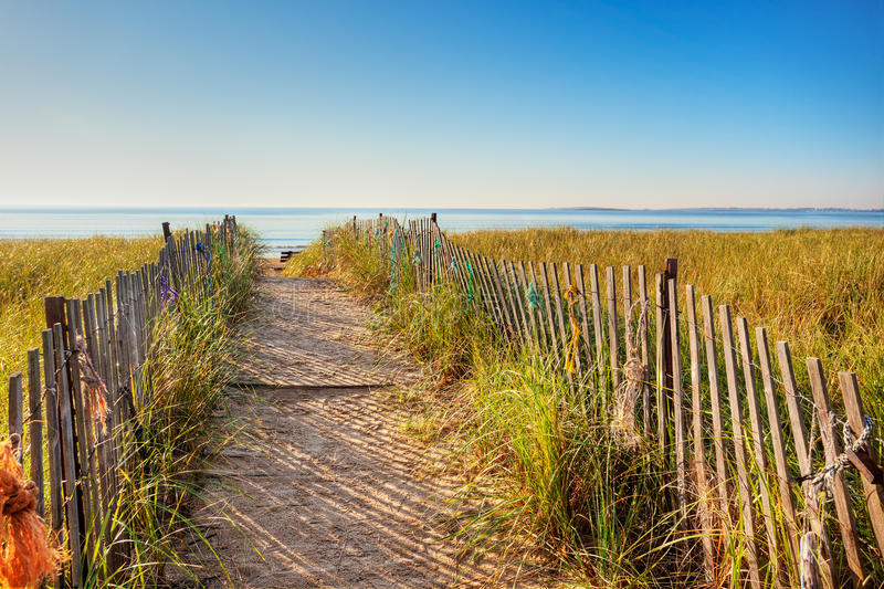 Maine boardwalk to the beach. Boardwalk through the dunes on the Maine coast with colorful ropes tied on the fence royalty free stock photography