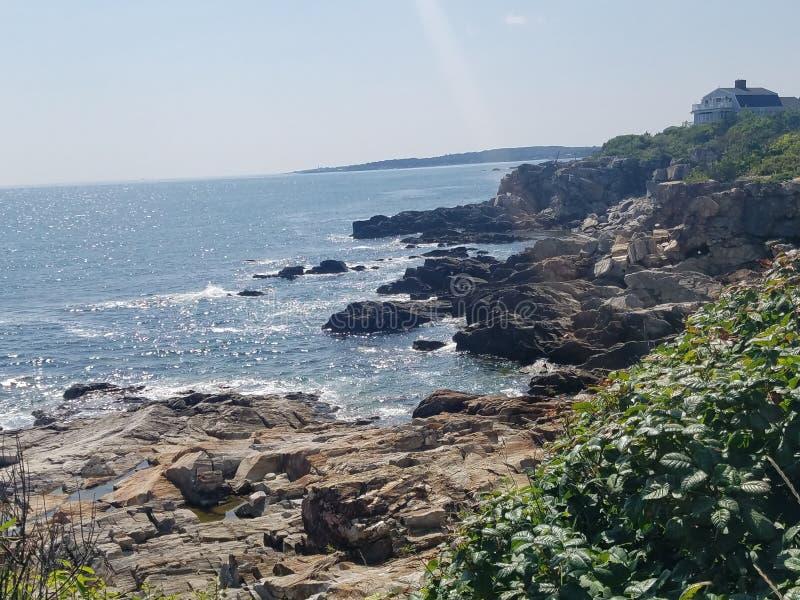 Maine, linha costeira da praia da rocha perto da casa clara fotografia de stock