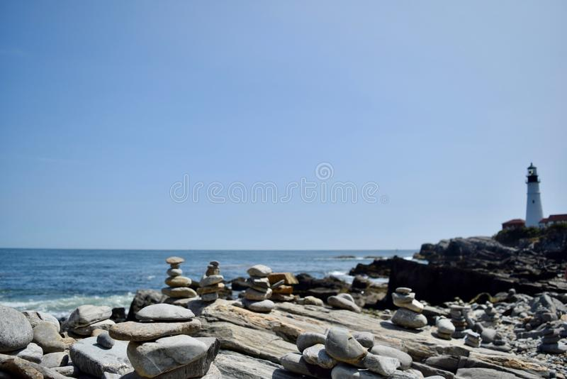 Maine`s Portland Head Lighthouse with rocks and cairns in the foreground. With the Atlantic ocean visible in the background stock photography
