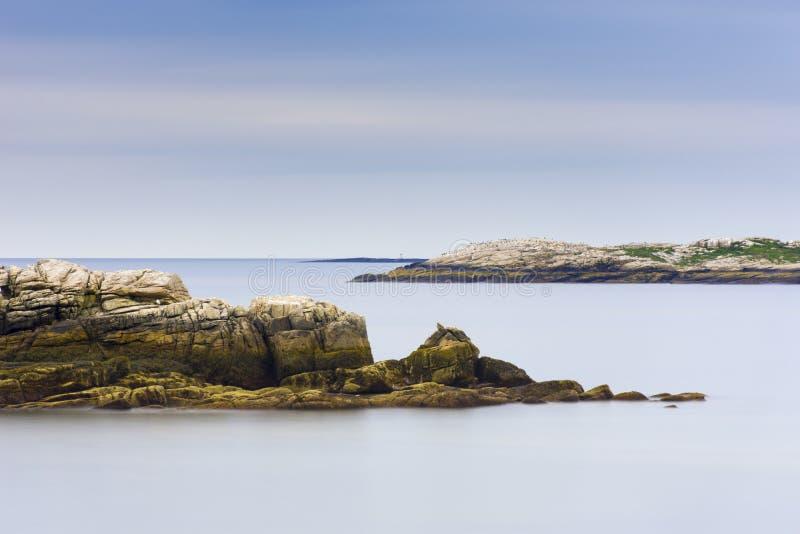 Maine stenig kustlinje med det släta havet och blå himmel fotografering för bildbyråer