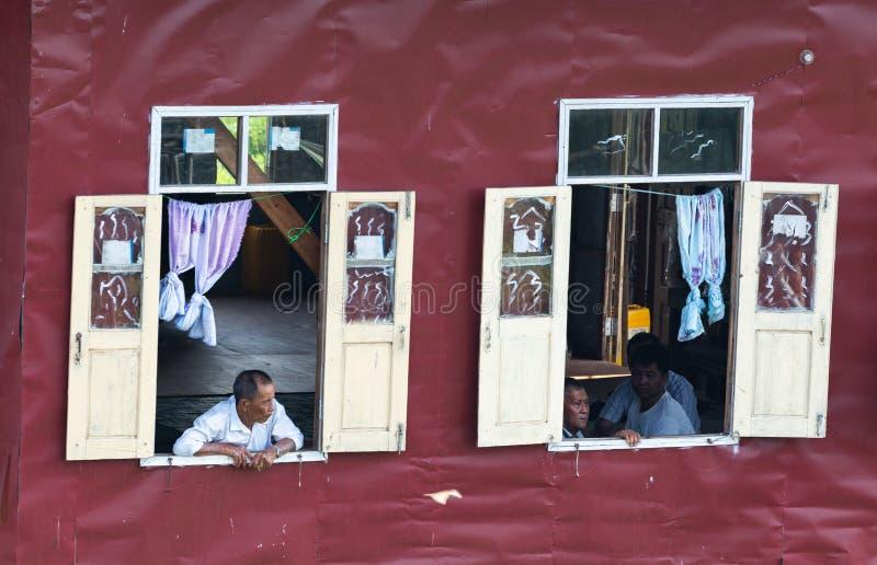 Maing Thauk, Myanmar - abril de 2019: viejo hombre birmano que mira fuera de la ventana flotante de la casa imágenes de archivo libres de regalías