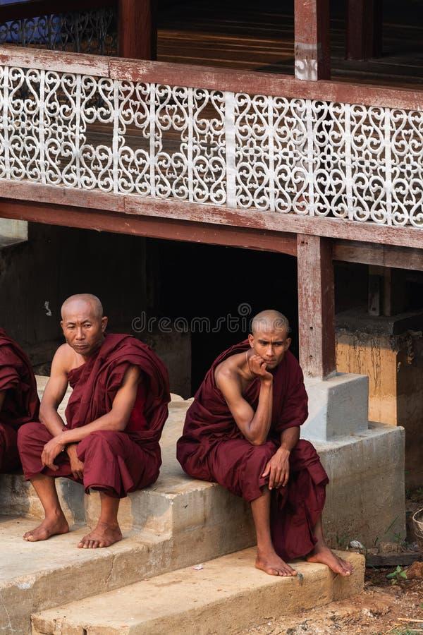 Maing Thauk, Myanmar - April 2019: Buddhistische Mönche sitzen auf einem Klosterportal am Inle See lizenzfreies stockfoto