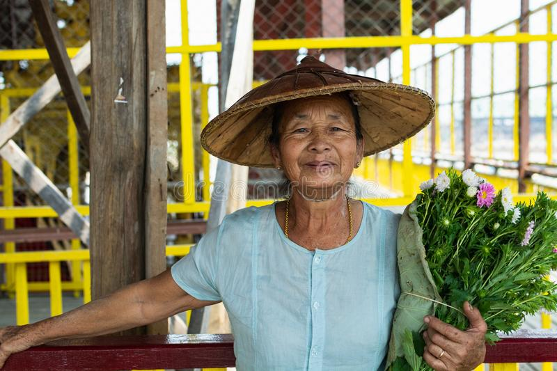 Maing Thauk, Myanmar - April 2019: portrait of an old Burmese woman in a bamboo hat and flowers stock photos
