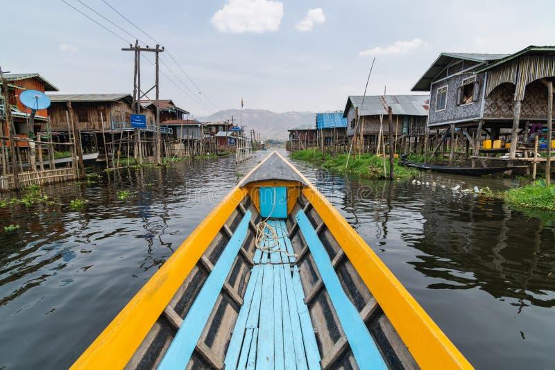 Maing Thauk, Myanmar - April 2019: Traditionele Birmaanse houten boot die door het dorp van Maing Thauk bij Inle-meer gaan stock foto's