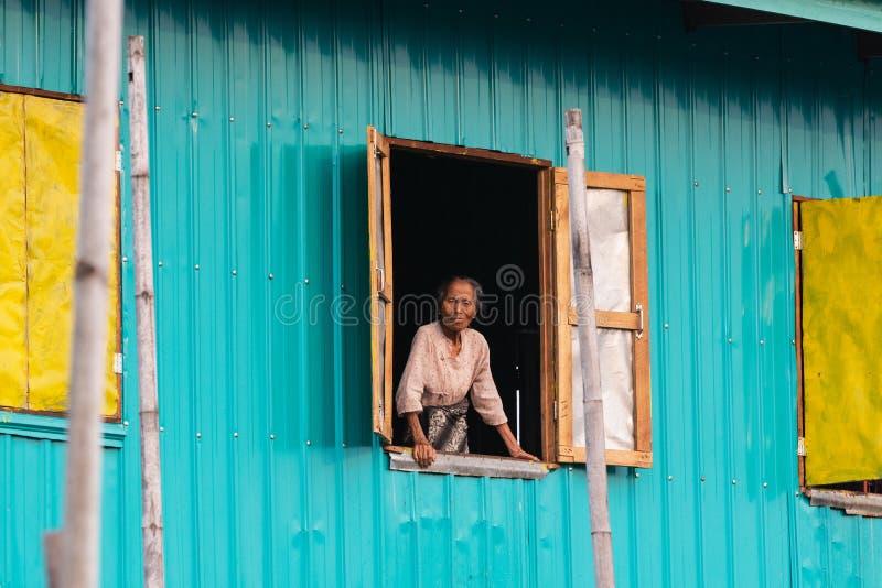 Maing Thauk, Myanmar - em abril de 2019: mulher idosa do birmanês que olha fora da janela de flutuação da casa fotografia de stock