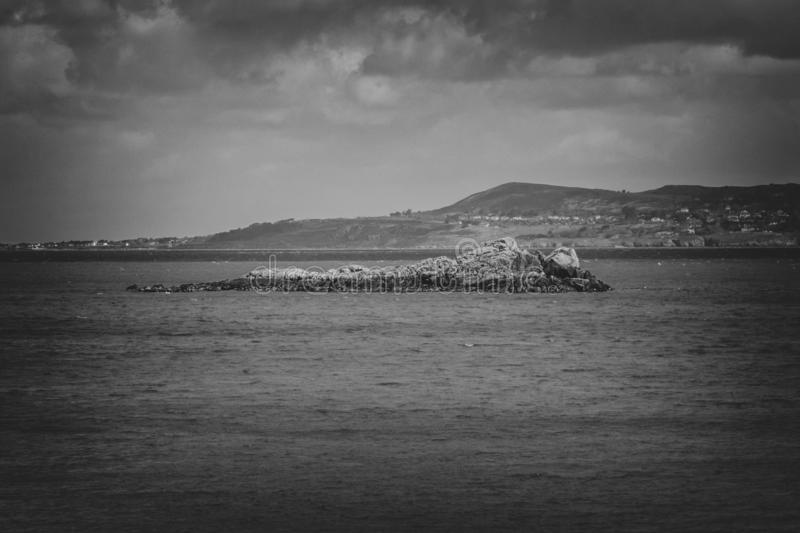 The Mainland Mirroring an Island from the Sea in Black and White stock image