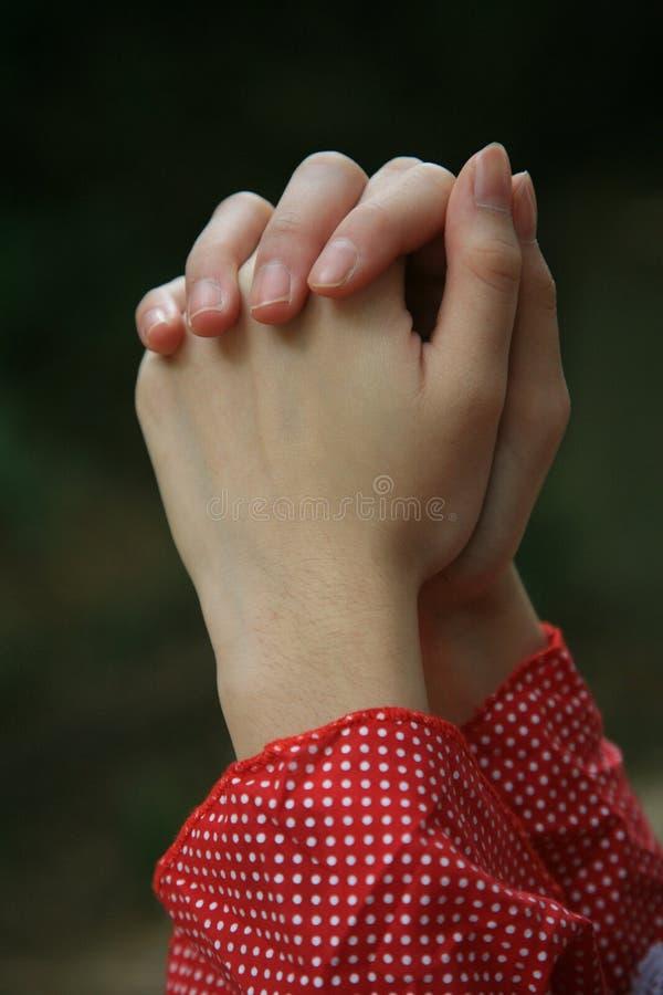 Mains étreintes dans la prière photographie stock
