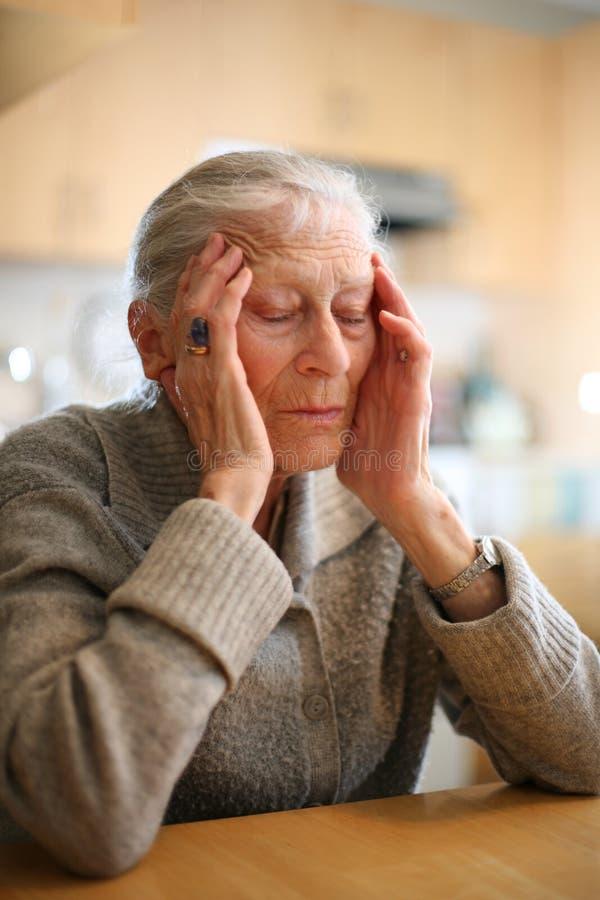 Mains aînées de woth de femme sur la tête images stock