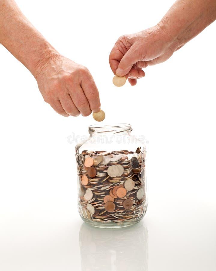 Mains aînées rassemblant des pièces de monnaie dans un choc en verre photographie stock libre de droits