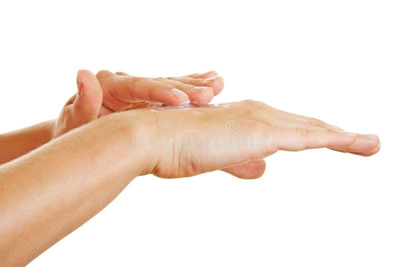 Mains appliquant la crème hydratante pour le traitement de peau photographie stock