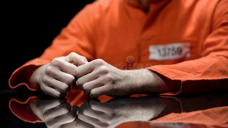 Mains arrêtées plan rapproché, prisonnier de personne parlant à l'avocat pendant l'interrogation photos stock