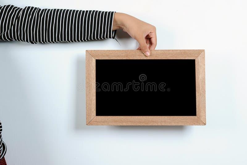 Mains asiatiques de femme tenant le tableau noir image stock
