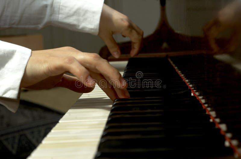Mains aux clés d'un piano photos libres de droits