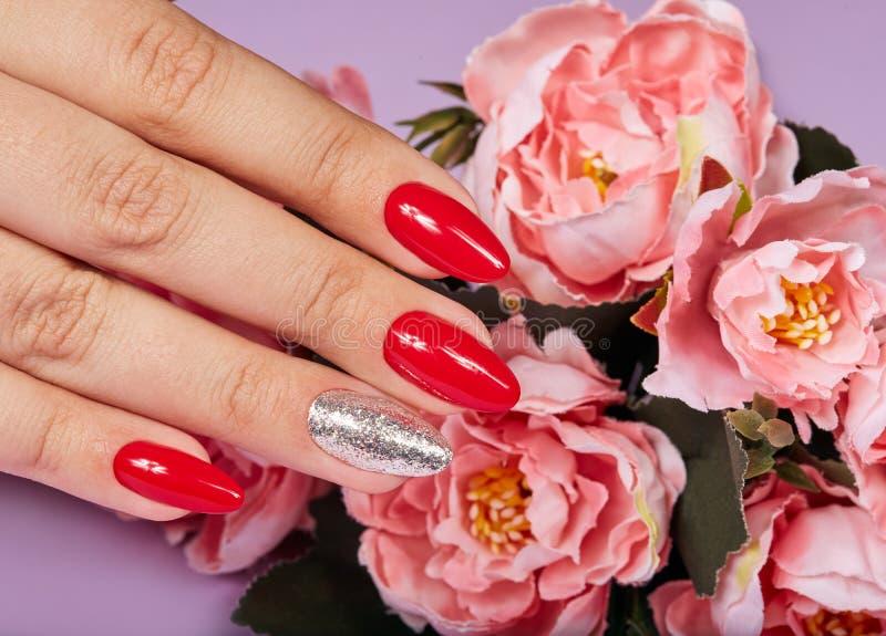 Mains avec de beaux ongles manucurés artificiels colorés avec le vernis à ongles rouge et argenté image stock