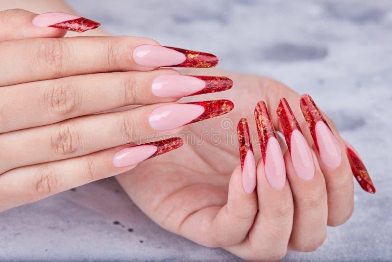 Mains avec de longs ongles manucurés français artificiels rouges photos stock