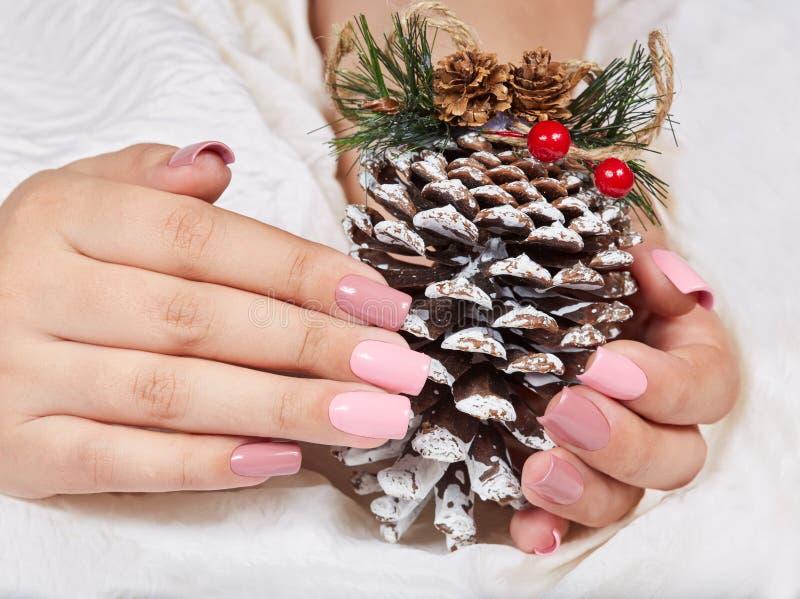 Mains avec de longs ongles manucurés roses artificiels tenant une décoration de Noël de pin photos stock