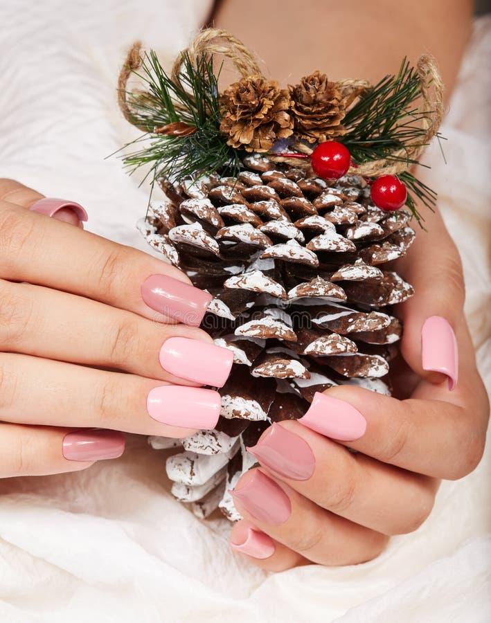 Mains avec de longs ongles manucurés roses artificiels tenant une décoration de Noël de pin image stock