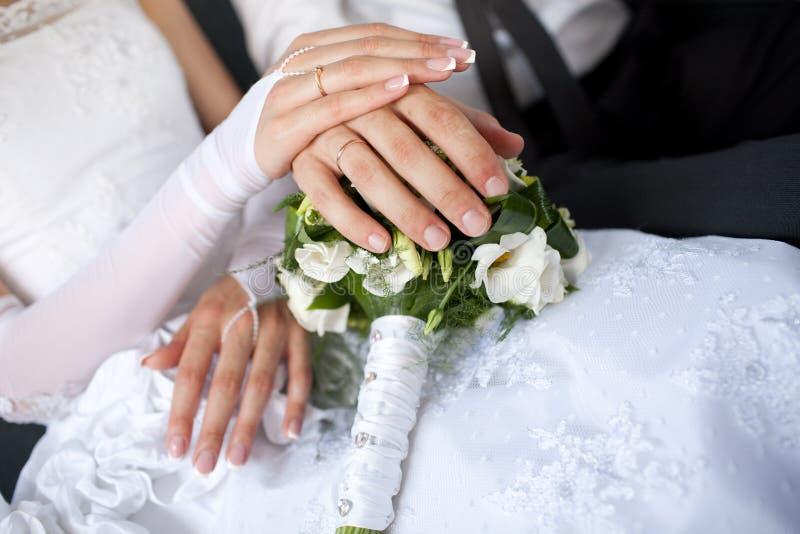 Mains avec des anneaux de mariage au-dessus du bouquet image libre de droits