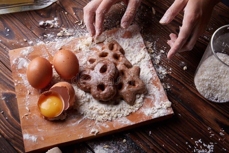 Mains avec des biscuits de chocolat à côté des ingrédients sur un fond de table Biscuits faisant cuire le concept photos libres de droits