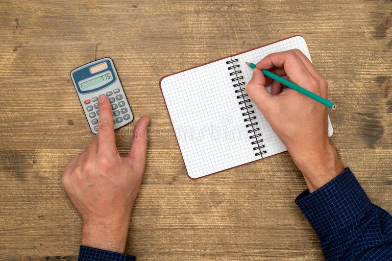 Mains avec la calculatrice et le bloc-notes images libres de droits