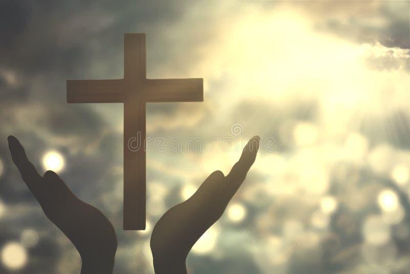 Mains avec la croix adorant au DIEU photos stock
