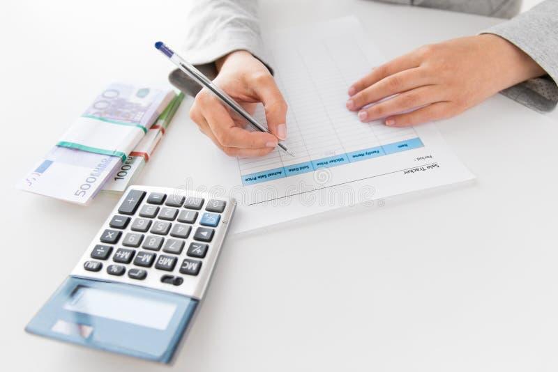 Mains avec la feuille d'impôt, la calculatrice et l'argent sur la table photo libre de droits